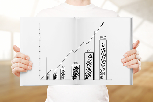 Male hands holding open book with business chart on blurry background with daylight